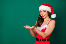 Photo Of Attractive Model Lady Hold Open Arms Demonstrating Showing New Sale Discount Decor Product Shopping Wear X-mas Snow Girl Costume Santa Cap Headwear Isolated Green Color Background