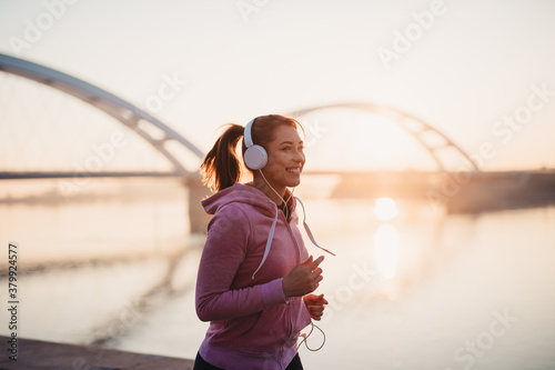 Fotografie, Obraz Beautiful young and fit woman in good shape running and jogging alone on city bridge street