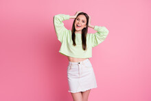 Photo Of Attractive Lady Hold Arms On Head Good Mood Summer Look Outfit Cheerful Meet Friends Wear Casual Green Crop Pullover Mini Denim Jeans Skirt Isolated Pink Color Background