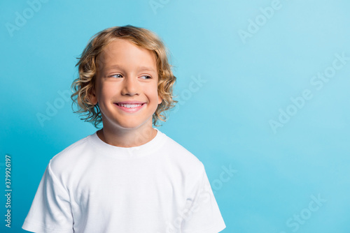 Photo of pretty boy look empty space beaming smiling wear white t-shirt isolated over blue color background