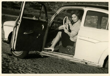 1960's Black And White Photo Of A Woman Sitting In The Drivers Seat Of A Car