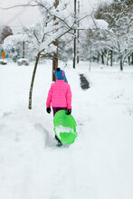 Girl Holding Green Disc Sled Walks Down A Snowy Sidewalk To The Park