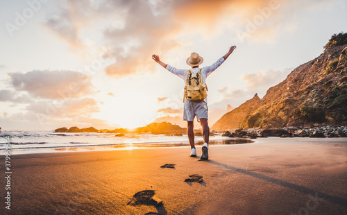 Fototapeta Happy traveller hiker with arms up enjoying freedom and sunset at the beach. Success, personal care, travel concept. obraz