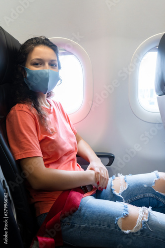 A girl in a medical mask on her face during a flight in the cabin. Air travel during a pandemic