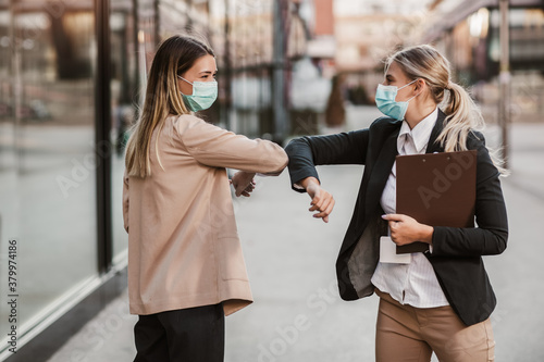 Obraz na plátně Businesswomen with safety masks greeting with elbow bump in front of office building