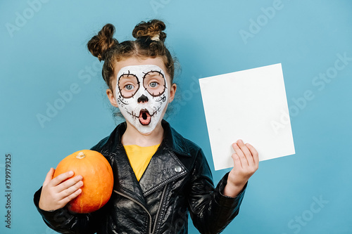 Fotomural Shocked little girl wears frightening makeup, hold pumpkin and white blank for advertisement, hiding behind a pumpkin, dressed in black leather jacket, isolated on blue background