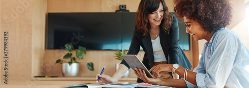 Creative female executives using digital tablet in office