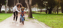Little Boy Learning To Ride Bicycle At Park With Mother
