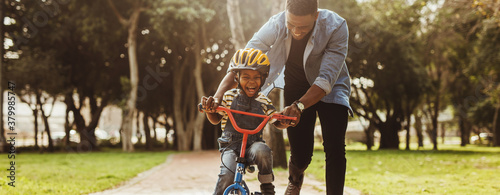 Father teaching his son cycling at park Fotobehang