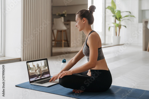 Fototapeta Yoga teacher conducting virtual yoga class at home on a video conference. Beautiful fit woman practicing online yoga in her living room with laptop. Home fitness and workout concept. Online training obraz