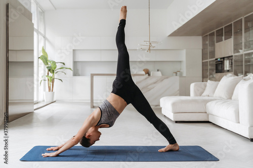 Young balanced woman in sportswear doing one legged dolphin yoga pose on mat at home in her living room, practicing yoga, meditation, workout, fitness Fotobehang
