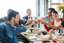 Group Of Mixed Race Young People Clinking Glasses During Informal Restaurant Lunch