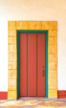 Vintage Red Wooden Door With A Sandstone Brick Border