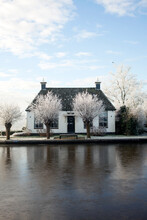 Dutch House With A Frozen Canal In Front