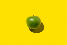 Green Apple On A Yellow Backgr...