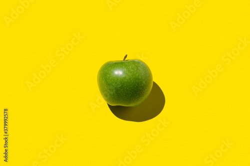 Photo Green apple on a yellow background. Hard shadow, overhead.