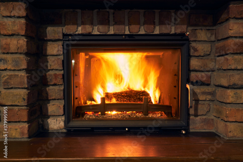 Fotografija fireplace and fire close view as object or background, brick wall