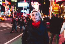 Young Woman Walking In Times Square At Night