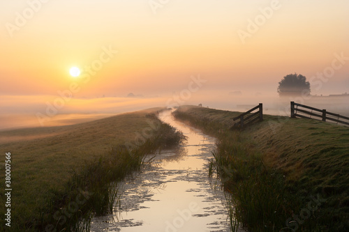 Fotomural Scenic landscape image with the sun rising above a layer of fog in the dutch pol