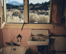 An Abandoned And Vandalized Bathroom With A Majestic Desert View