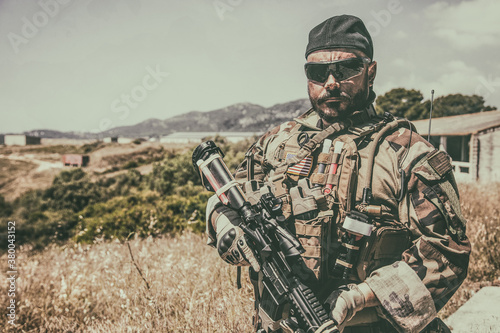 Vászonkép Navy SEALs fighter in ballistic goggles, equipped military ammunition and body armour, holding service rifle, looking in camera while standing outdoors