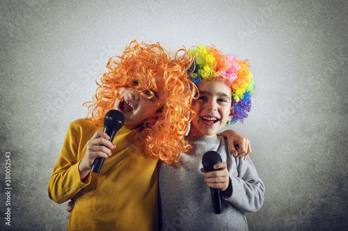 Fototapeta Two child sing a song with microphone and funny wig