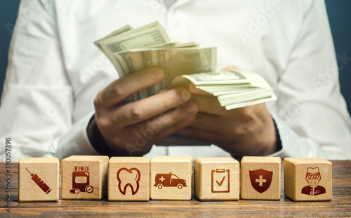 A man counts money over blocks with medical attributes symbols Canvas Print