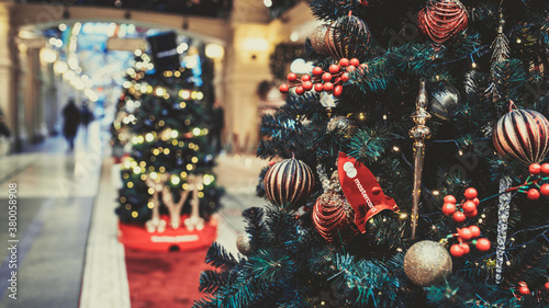 Fototapeta Close up of part of Christmas tree with different christmas toys and garland in shopping center. Coniferous tree with decorative adornments to create festive mood during holiday celebration obraz