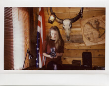 Instant Film Photo Of Yang Women With Camera In The Wooden Cabin With Vintage Map And Skull On The Wall