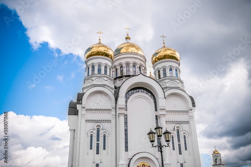 Golden domes, cupolas with Eastern Orthodox crosses on a white Church against a Canvas Print