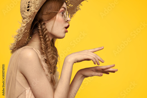 Portrait of a pretty woman with pigtails and with a hat on her head on a yellow Wallpaper Mural