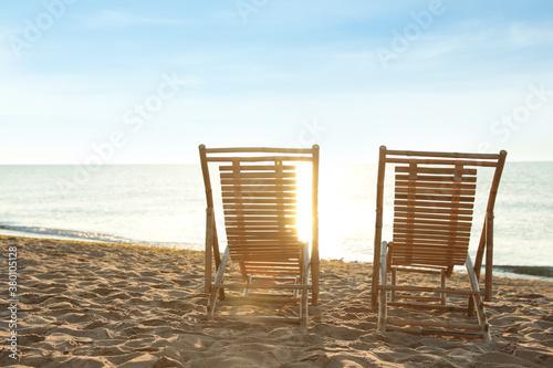 Obraz Wooden deck chairs on sandy beach. Summer vacation - fototapety do salonu