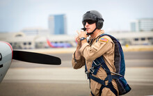Fighter Pilot Straping On Helmet And Goggles While Walking Near Runway Toward Marchetti SIAI SF260 Fighter Airplane
