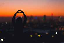 Woman In Silhouette Making Heart Shape With Hands On Sunset