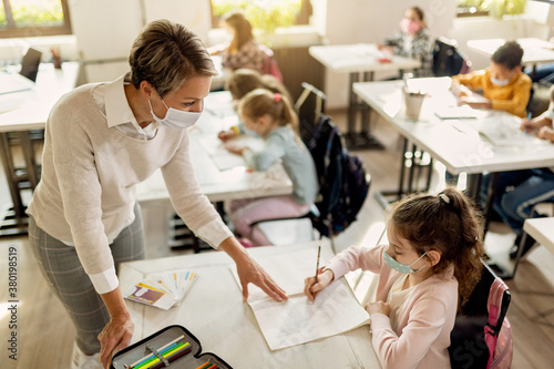 Female teacher wearing face mask while assisting schoolgirl during a class in the classroom Fototapeta