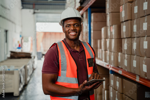 Factory worker smiling holding digital tablet organising parcels in warehouse
