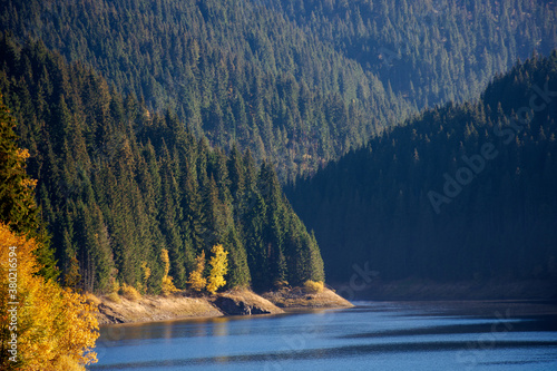 Fototapeta mountain lake in autumn season. beautiful countryside scenery on a sunny morning. bright blue sky with fluffy clouds reflecting on the water surface obraz