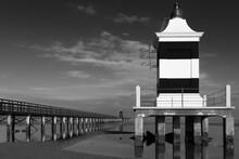 Black And White Image Of A Pier And A Lighthouse Facing The Adriatic Sea.  Lignano Sabbiadoro, Friuli Venezia Giulia, Italy.