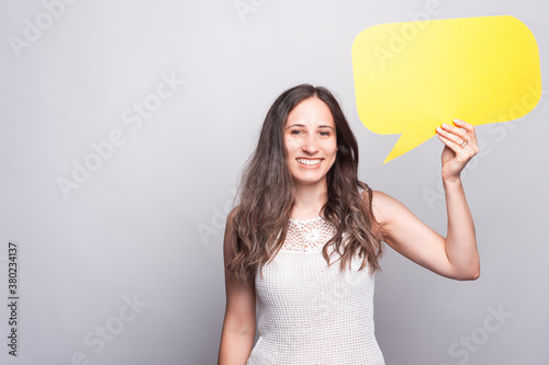 Fototapeta Happy young woman is smiling at the camera and holding a yellow blank speech bubble obraz
