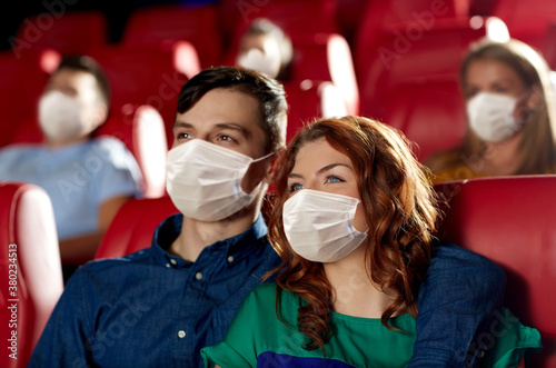Fototapeta cinema, entertainment and pandemic concept - couple wearing face protective medical masks for protection from virus disease watching movie in theater obraz