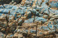 Close Up View Bright Vivid Orange Brown Yellow Stone Rock Shabby Cliff Cracks Texture Mountains. Concept Of Geology, Beauty Power In Nature. Natural Summer Composition Landmark Background Design