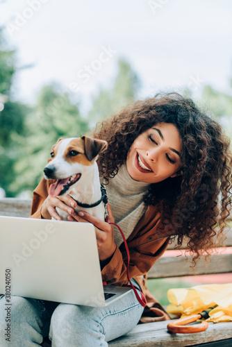 Fototapeta joyful freelancer cuddling jack russell terrier dog while sitting on bench with laptop obraz