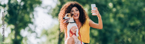 Obraz horizontal concept of excited woman taking selfie on mobile phone with jack russell terrier dog - fototapety do salonu