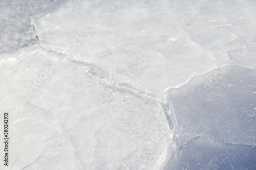 Close-up of cracked ice on a frozen lake in the winter, viewed from the front Wallpaper Mural
