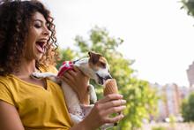 Selective Focus Of Young Woman With Open Moth Looking At Dog Licking Ice Cream