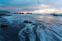 Sunrise At A Beautiful Beach With Golden Sunlight Reflected On Seawater And Turbulent Waves Rushing Onto The Shore Under Dramatic Dawning Sky At Wai'ao Coast, Yilan ( Ilan ), Taiwan (Long Exposure)