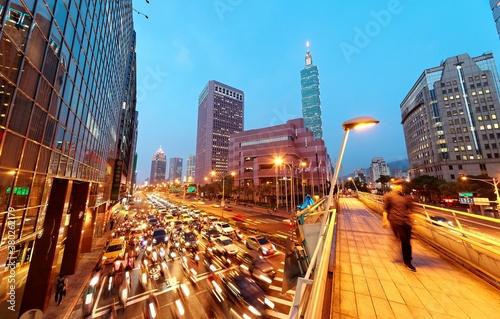 Fotografía Evening view of a pedestrian footbridge over a busy street corner at rush hour &