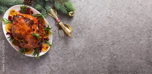 Fototapeta Christmas table with baked chicken is festively decorated with candles. top view obraz
