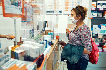 Woman shopping at pharmacy, buying medicines, wearing face mask to cover mouth and nose during pandemic coronavirus outbreak