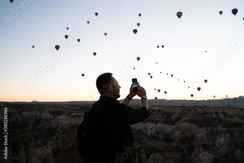 Foto Adult male capturing photo of hot air balloons in terrain